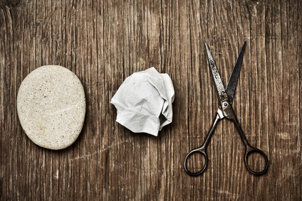 high-angle shot of a rock, a crumpled paper and an old pair of scissors, depicting the rock-paper-scissors game, on a rustic wooden surface