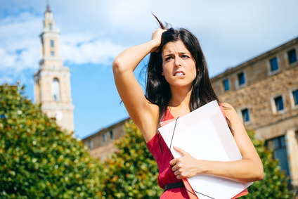 Worried female student in problems. Stressed young woman at university campus after educational fail.
