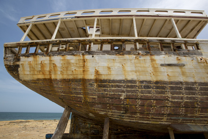 Old shipwreck standing on the beach with the sea in the background with faded paintings against a blue sky. Margarita Island. Venezuela