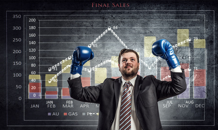 Young businessman in boxing gloves and infographs at background