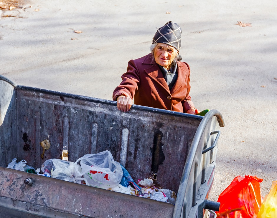 Homeless woman is searching for food in garbage dumpster. Woman in poverty is searching something in container.